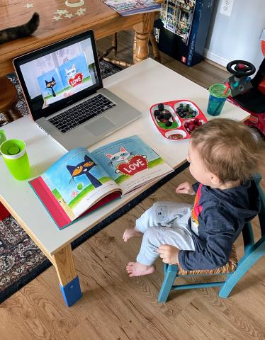 Child sitting at desk watching Story Time on computer and following along with book
